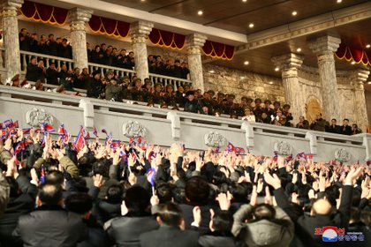 Kim Jong Un saluda a sus partidarios desde un palco donde observó todo el desfile militar (KCNA via REUTERS)